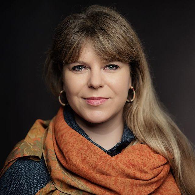 zdjęcie przedstawia Aleksandrę Zińczuk, redaktorkę naczelną magazynu Kultura Enter. To sympatyczna młoda kobietą z długimi blond włosami. Ma kolczyki. Ubrana jest w szarą bluzkę i pomarańczowy szalik