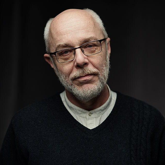 Zdjęcie przedstawia Grzegorza Rzepeckiego, dyrektora Warsztatów Kultury. To sympatyczny, starszy mężczyzna, z siwymi włosami po bokach głowy, na środku łysina. Siwa broda i wąsy. Ma okulary. Ubrany jest w czarny sweter i białą koszulę